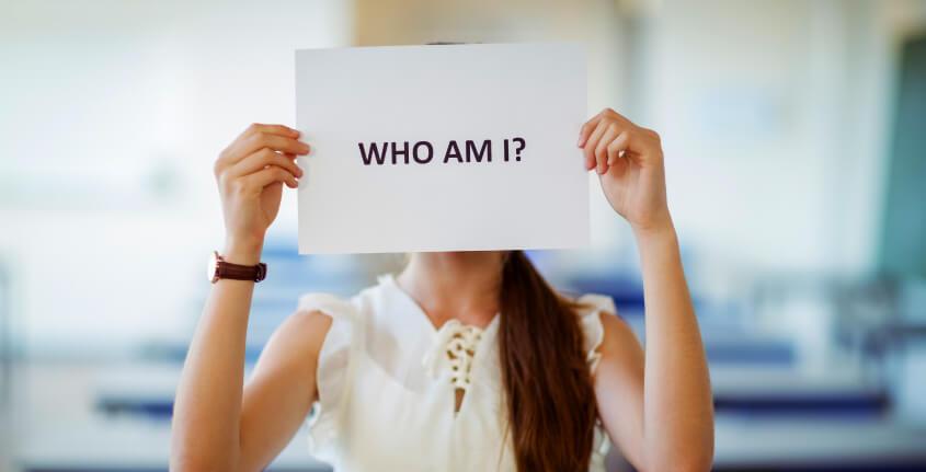 """mulher segurando cartaz perguntando, """"quem sou eu""""."""