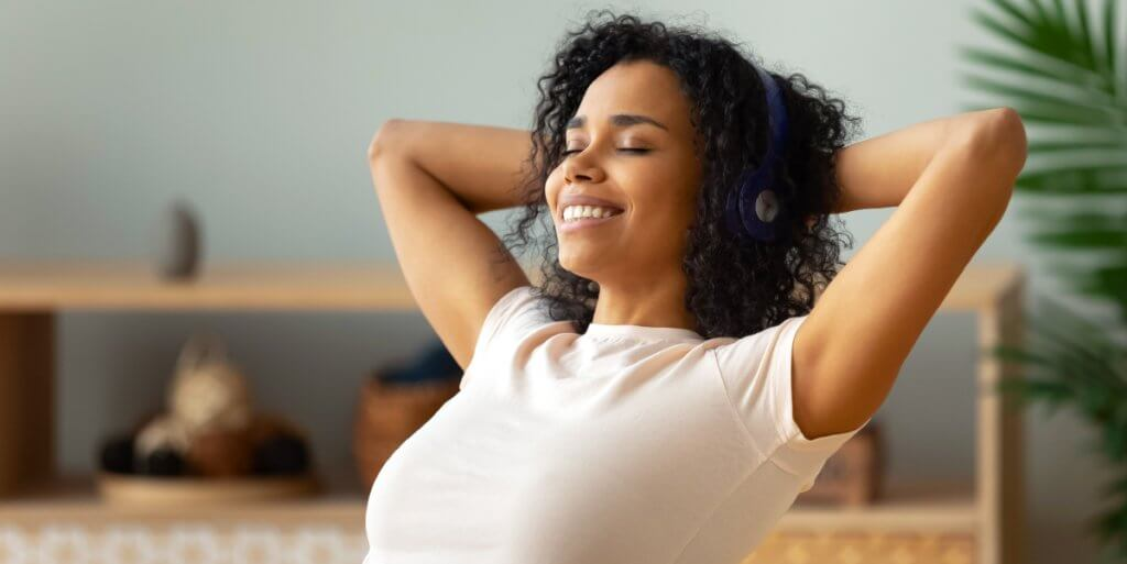 uma mulher ouvindo música com um fone e sorrindo