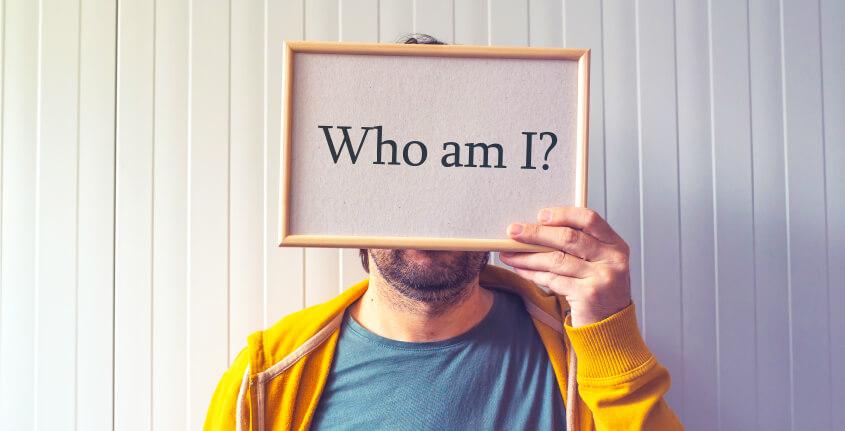 """homem segurando placa escrito """"que sou eu?"""""""