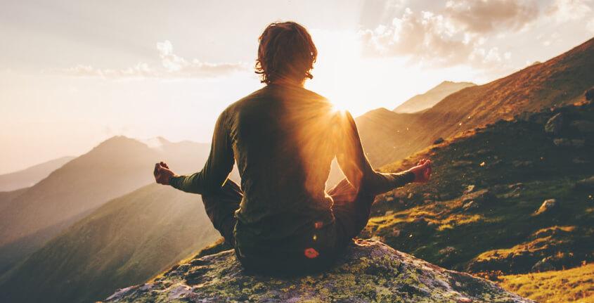 Homem meditando em cima de uma montanha