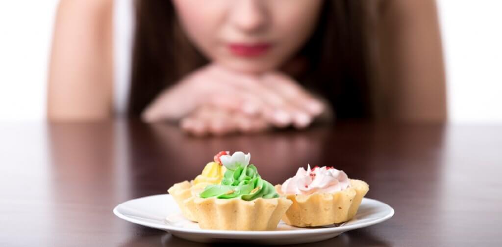 uma mulher encarando doces